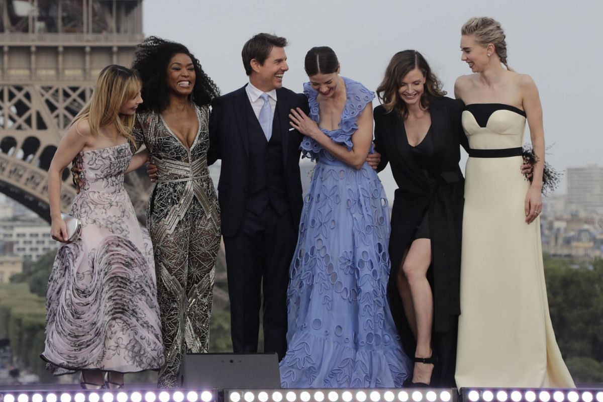 Tom Cruise (centre) and cast members (from left) Alix Benezech, Angela Bassett, Michelle Monaghan, Rebecca Ferguson and Vanessa Kirby joking on the stage in front of the Eiffel Tower on July 12, 2018.