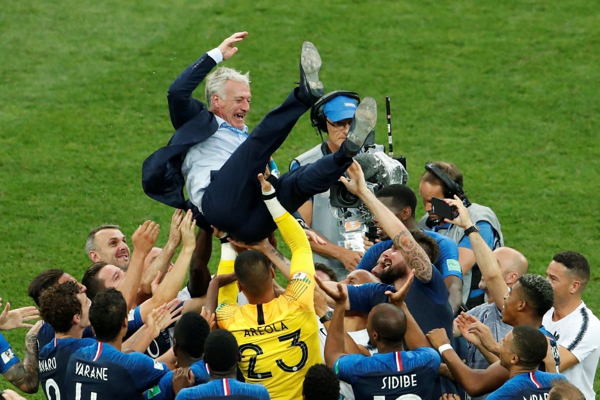 France coach Didier Deschamps is thrown into the air by his players as they celebrate after winning the 2018 Fifa World Cup, on July 15, 2018.
