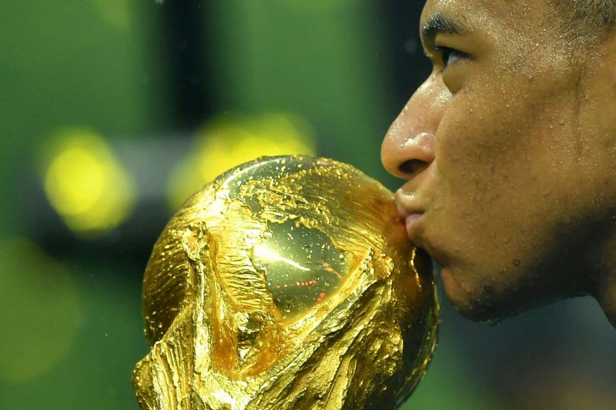 France's Kylian Mbappe kisses the trophy to celebrate winning the 2018 Fifa World Cup, on July 15, 2018.