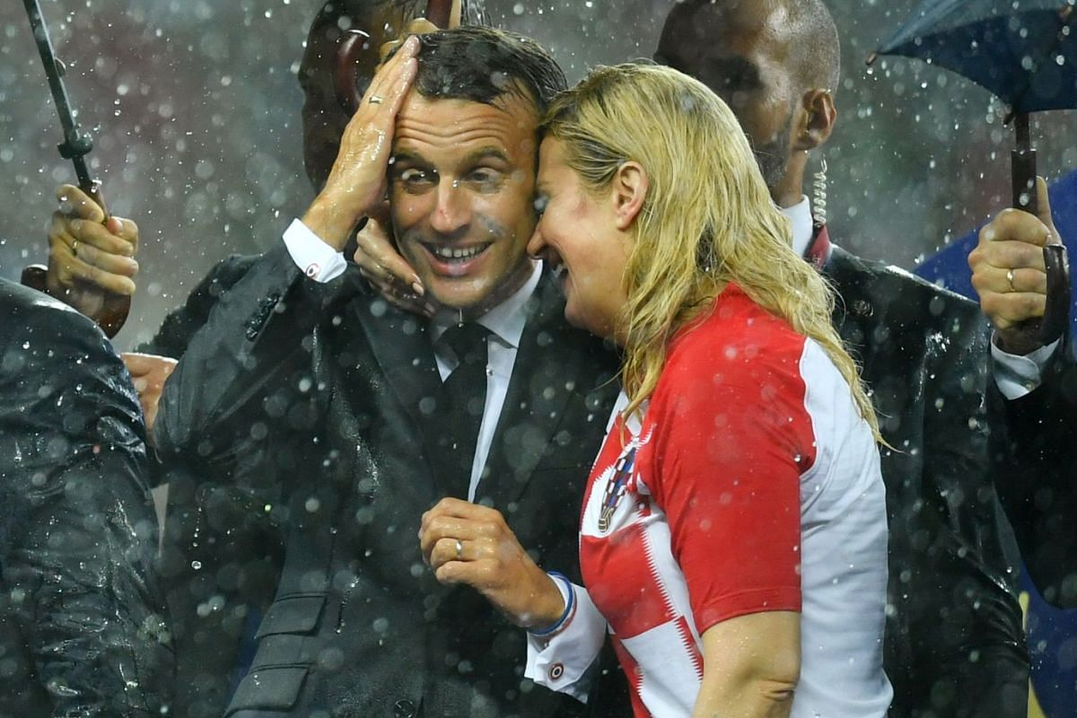 President of Croatia Kolinda Grabar-Kitarovic (right) and President of France Emmanuel Macron were soaked and left without protection as the rain fell on the Luzhniki Stadium in Moscow, Russia, before more umbrellas came, on July 15, 2018.