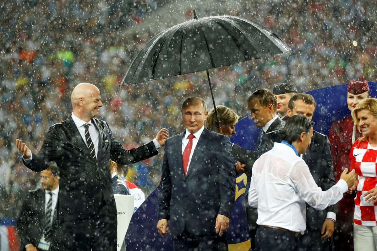 President of Russia Vladimir Putin (centre) was offered the first umbrella during the downpour at the award presentation, a move that has social media users pointing out the favouritism shown to Russia's controversial leader.