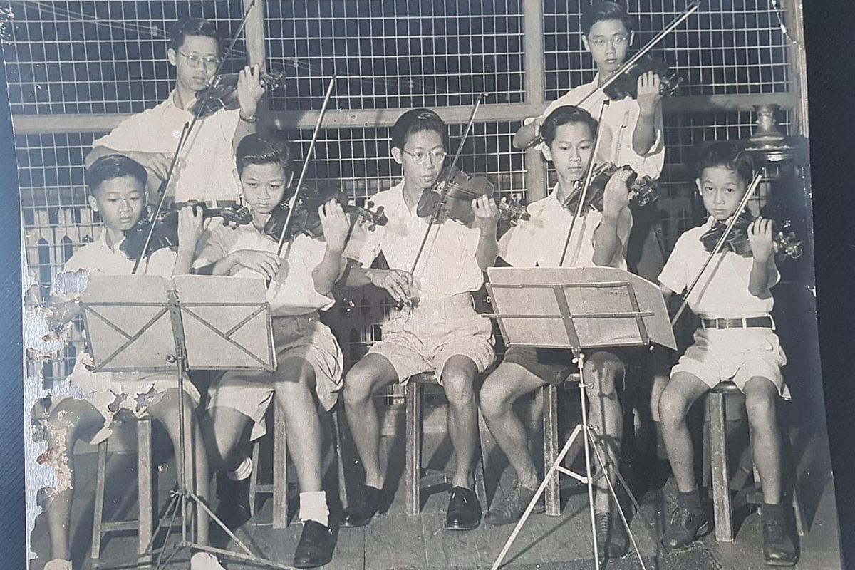 Mr Koh Seow Chuan (right) in 1951, at 12 years old, playing the violin with his brothers. A stamp collector, Mr Koh had part of his collection (above) sent to different space stations. Mr Koh in 1956 with his swimming trophies (left), before departin