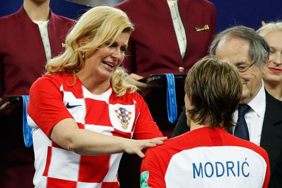 Croatia's midfielder Luka Modric is congratuled by by Croatian President Kolinda Grabar-Kitarovic upon receiving the Golden Ball award for best player during the medals ceremony after the Russia 2018 World Cup final football match between France and