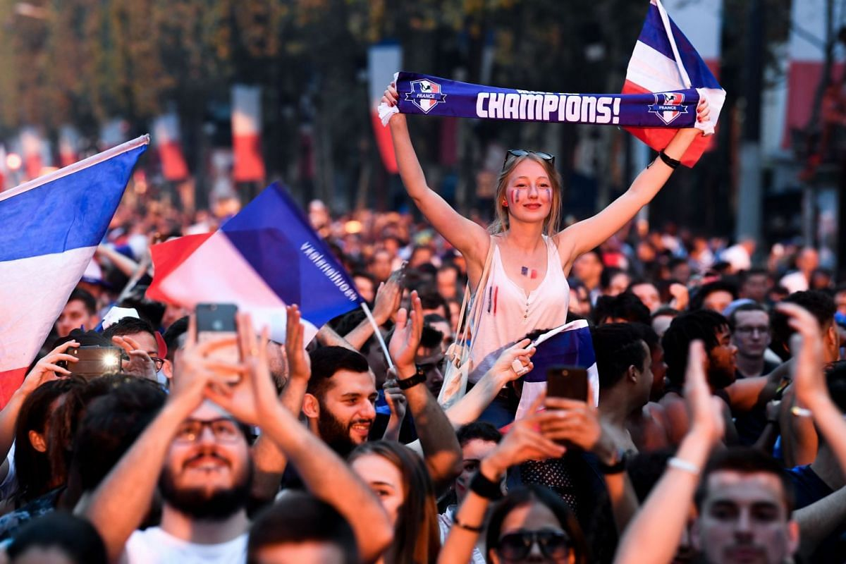 People celebrating France's victory in the Russia 2018 World Cup final football match between France and Croatia, on the Champs-Elysees avenue in Paris, on July 15, 2018.