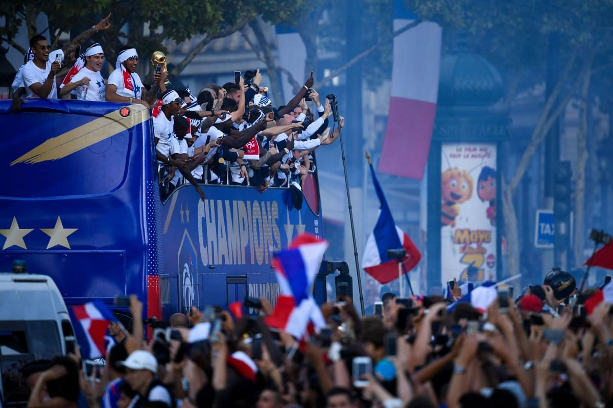 France's fans wave French national flag, light flares and cheer France's team players as they celebrate on the roof of a bus while parading down the Champs-Elysee avenue after winning the Russia 2018 World Cup final football match, in Paris, France J