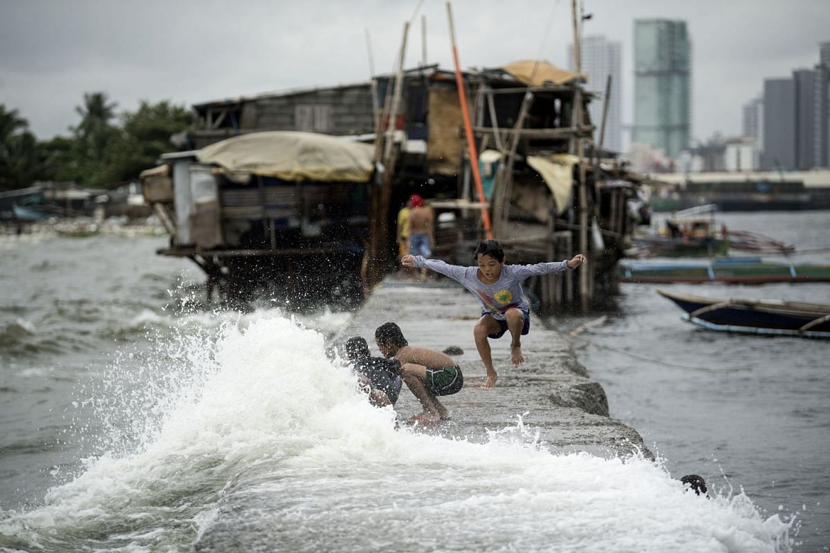 Children living on houses erected on the sea wall of Manila Bay play with waves caused by the Tropical Depression Henry that brought heavy rains in Metro Manila and the northern part of Luzon on July 16, 2018. PHOTO: AFP