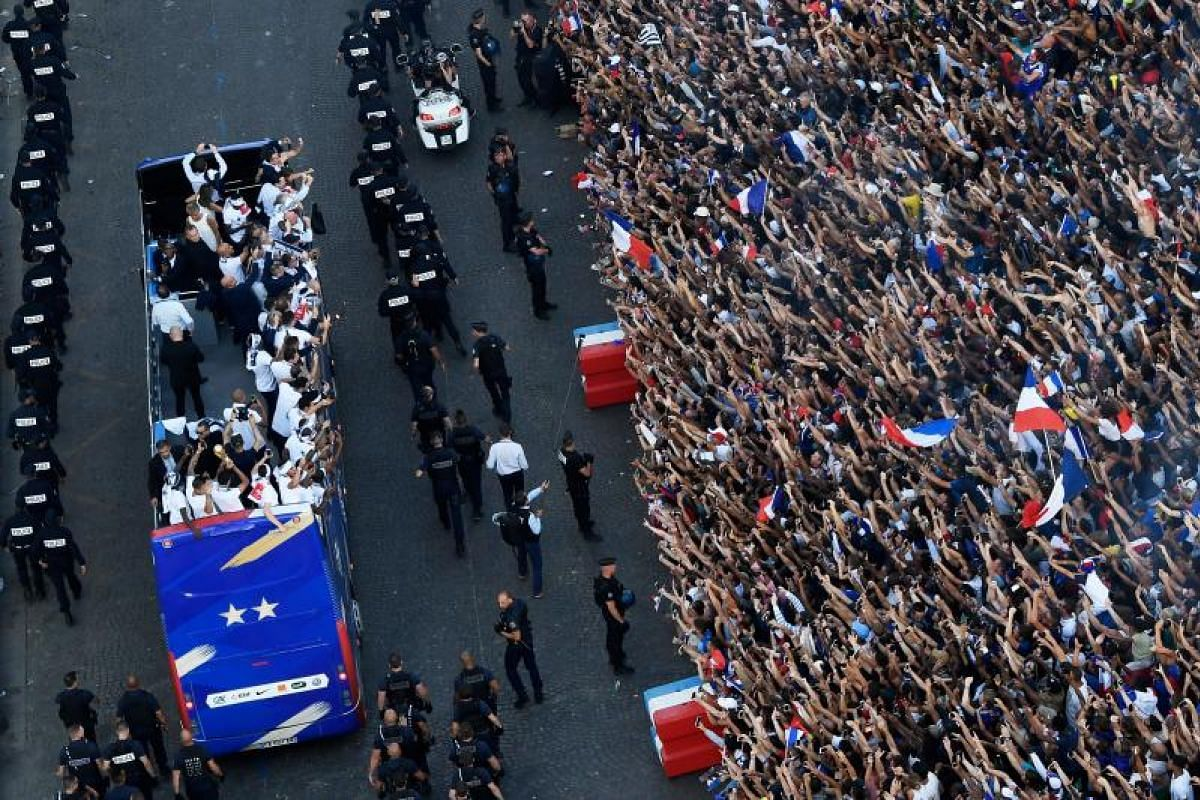 Fans greet France's national football team players as they celebrate on the roof of a bus while they parade down the Champs-Elysee avenue in Paris, on July 16, 2018 after winning the Russia 2018 World Cup final football match.