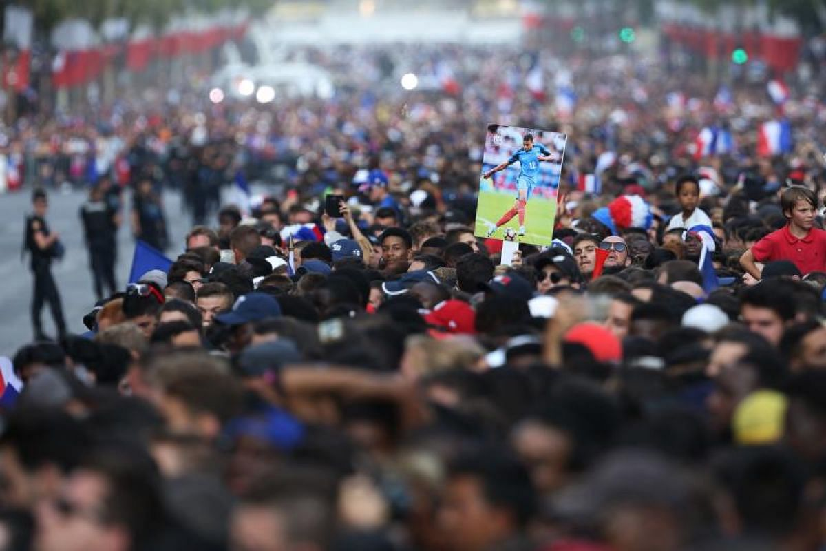 A fan holds a picture of France's forward Kylian Mbappe next to supporters waving French national flags while they greet France's national football team players during a parade down the Champs-Elysee avenue in Paris, on July 16, 2018.