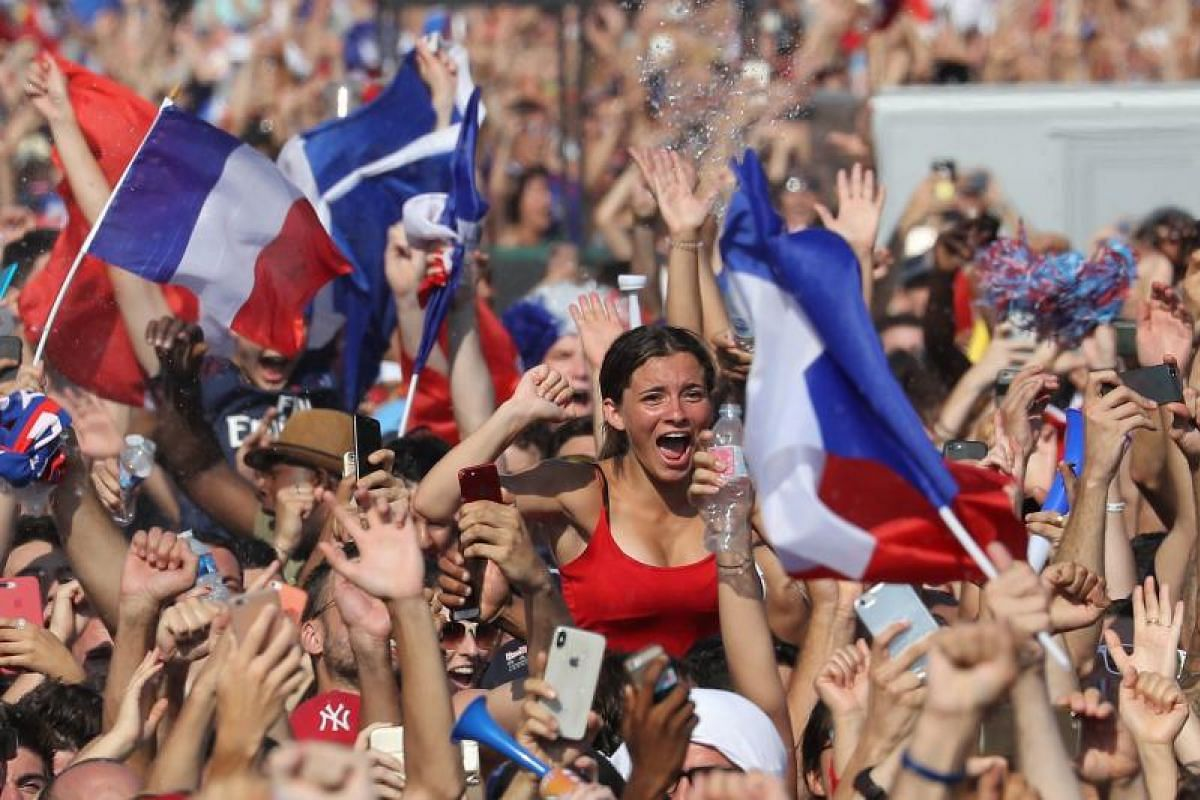 Supporters cheer as they greet France's national football team players as they parade down the Champs-Elysee avenue in Paris, on July 16, 2018.
