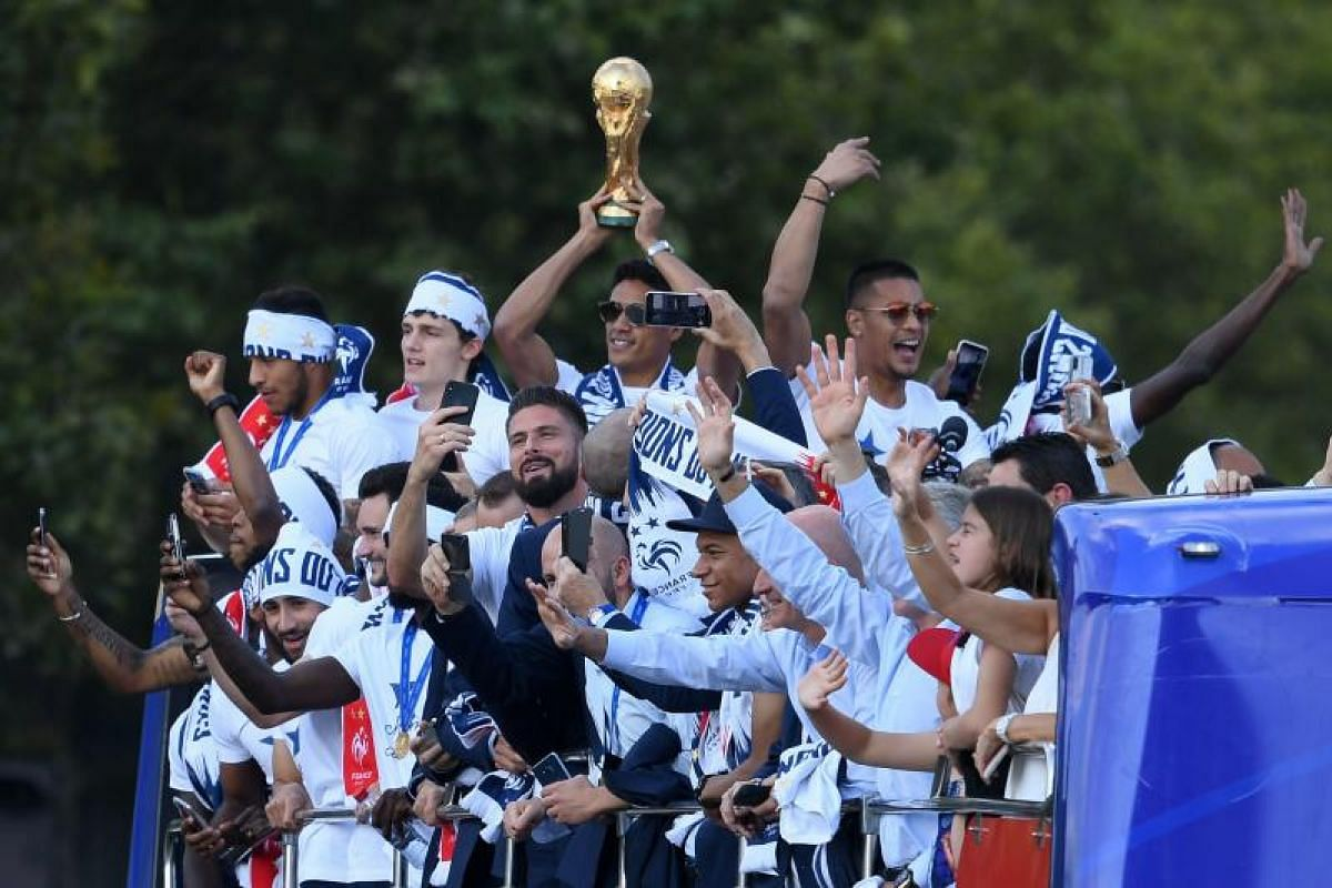France's defender Raphael Varane (centre) holds the trophy as he celebrates with teammates on the roof of a bus while parading down the Champs-Elysee avenue in Paris, on July 16, 2018.