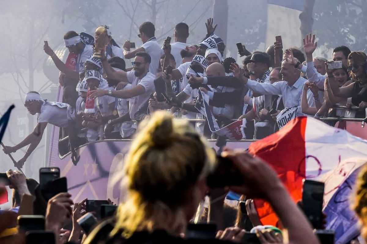 A fan takes pictures with her mobile phone of defender Adil Rami (right) holding the trophy and celebrating with teammates on the roof of a bus while parading down the Champs-Elysee avenue in Paris, on July 16, 2018.