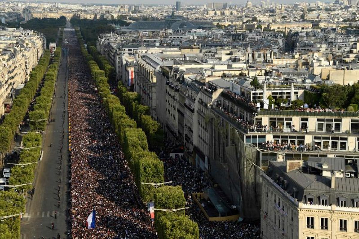 Supporters gather on the Champs-Elysees avenue in Paris as they await the arrival of the French national football team on July 16, 2018.