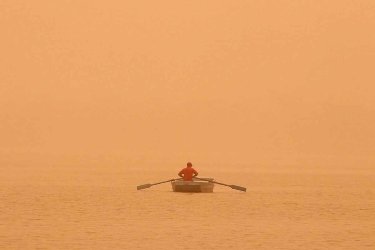 A man rowing amid haze on the Sukhna lake in Chandigarh on June 15, when the PM2.5 level in the Indian city hit an alarming 572, according to the Chandigarh Pollution Control Committee observatory.