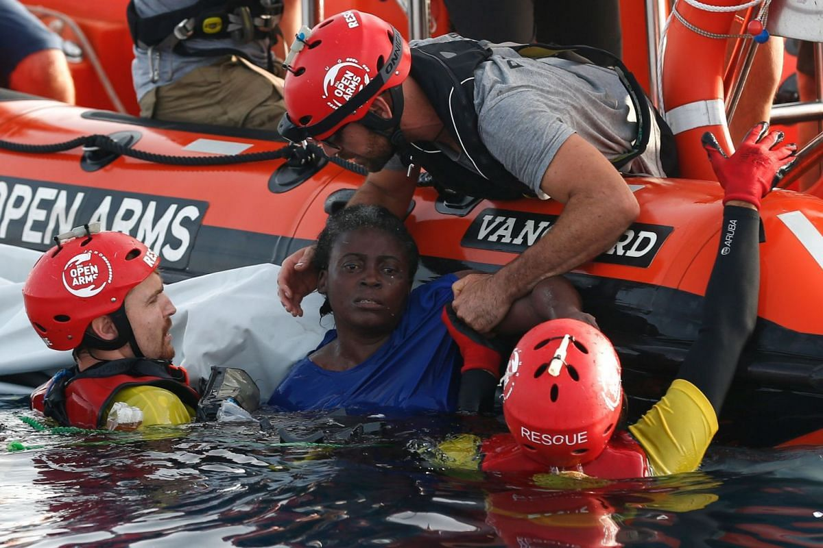 Members of the Spanish NGO Proactiva Open Arms rescue a woman in the Mediterranean open sea about 85 miles off the Libyan coast on July 17, 2018. PHOTO: AFP