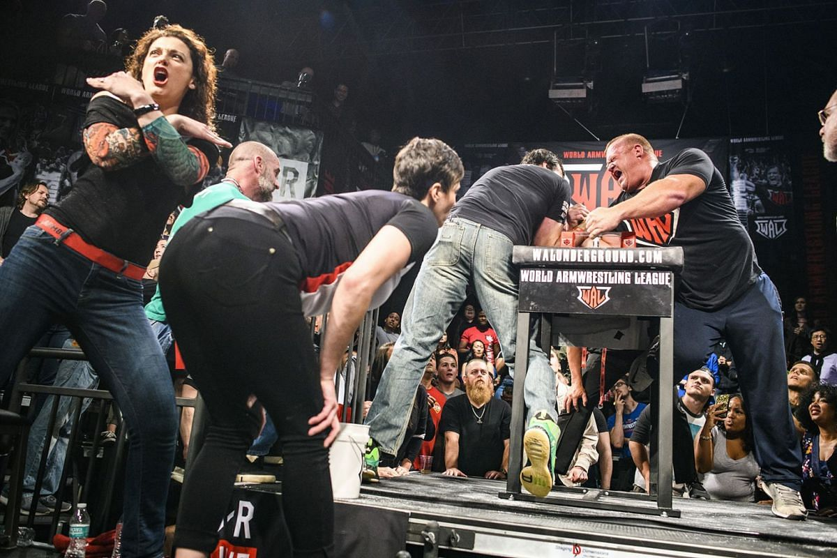A photo released on July 18, 2018, shows Jodi Larratt, left, signaling the match is over as her husband, Devon Larratt, pinned Jerry Cadorette to win the final heavyweight match of the night at the World Armwrestling League Supermatch Showdown Series