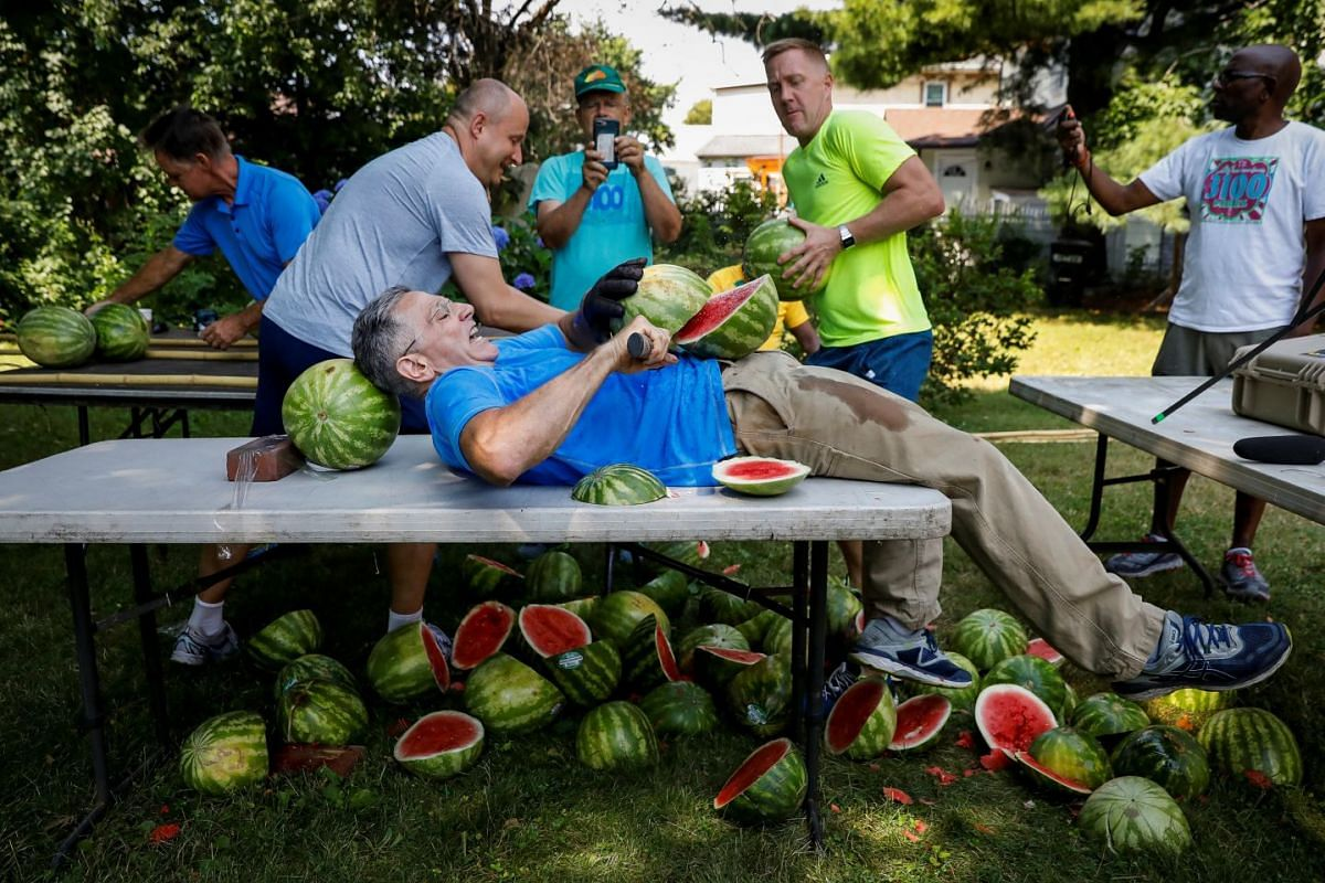 Ashrita Furman, who holds more Guinness World Records than anyone, attempts to set a new record for slicing the most watermelons in half on his own stomach in one minute in New York City, U.S., July 17, 2018. PHOTO: REUTERS