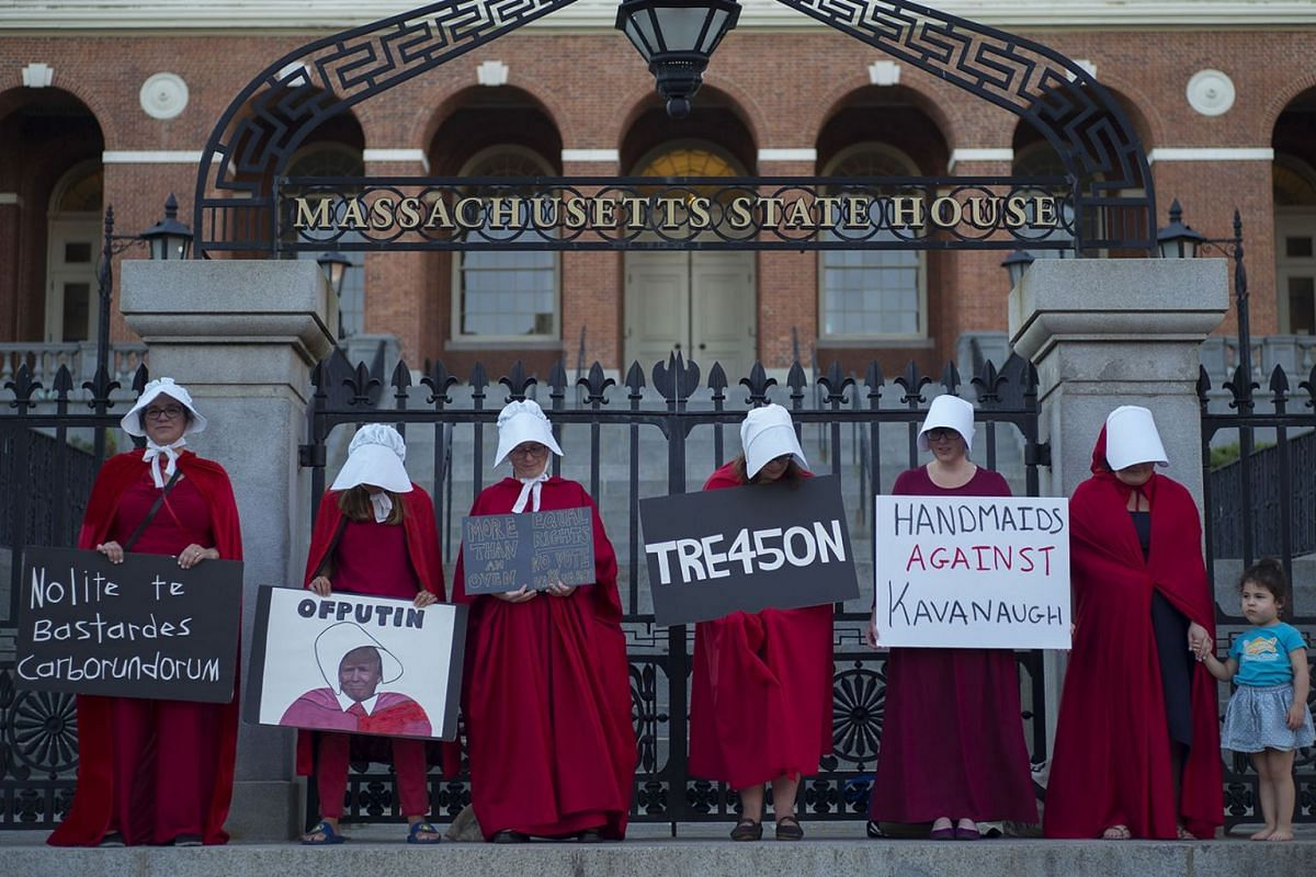 Women dressed in Handmaids cloaks and hoods, hold signs in protest of United States President Donald J. Trump while standing in front of the Massachusetts State House in Boston, Massachusetts, USA, July 18, 2018. PHOTO: EPA-EFE