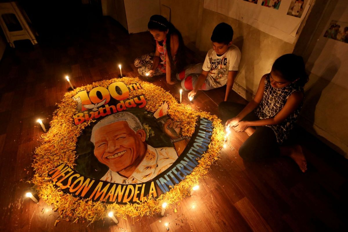 Children light candles beside a painting commemorating South African revolutionary Nelson Mandela's 100th birth anniversary at an art school in Mumbai, India, July 18, 2018. PHOTO: REUTERS