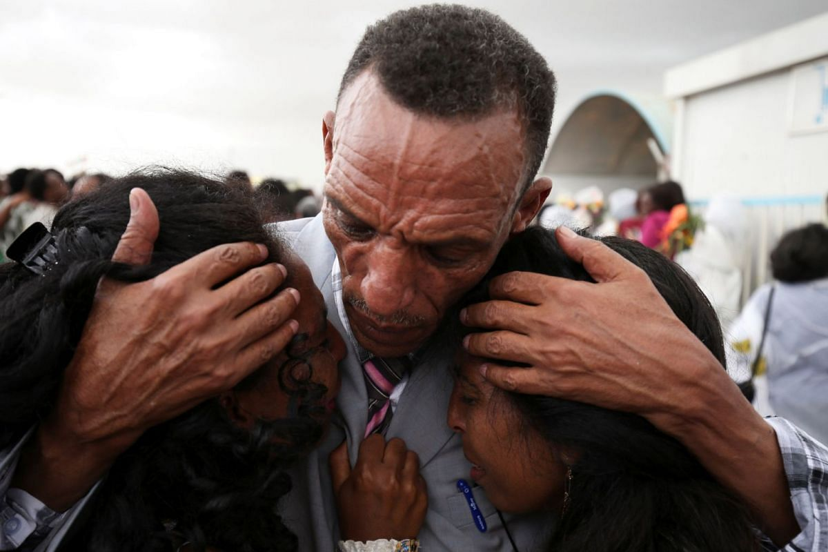 Adisalem Abu, reacts as he embraces his twin daughters, after meeting them for the first time in eighteen years, at Asmara International Airport after arriving aboard the Ethiopian Airlines flight in Asmara, Eritrea July 18, 2018. PHOTO: REUTERS
