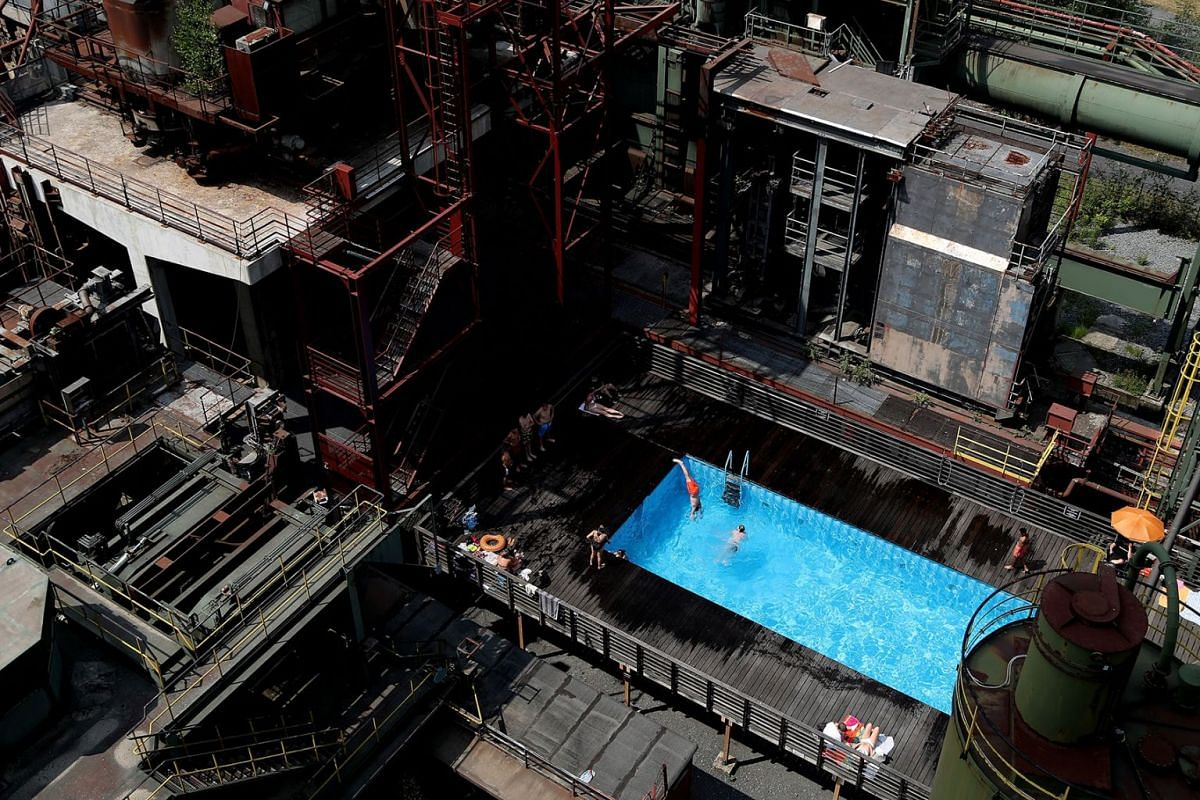 People enjoy the Works Swimming Pool in the yard of the former coking plant of the 'Zeche Zollverein' industrial complex, in Essen, Germany, July 18, 2018, which is an UNESCO world heritage site since 2001. PHOTO: EPA-EFE
