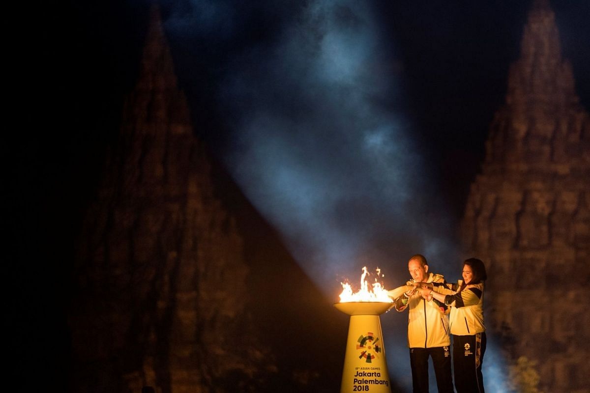 Indonesian badminton legend Susi Susanti (R) and former tennis star Yustedjo Tarik (L) light the torch during the 2018 Asian Games Torch Relay ceremony at Prambanan Temple complex, Sleman, Yogyakarta, Indonesia July 18, 2018 in this photo taken by An