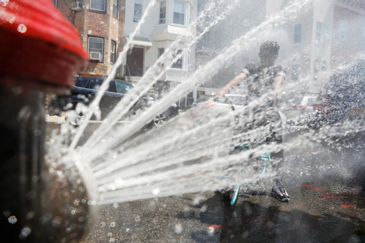 A boy on a bicycle cools off from the extreme heat from an opened fire hydrant in Brooklyn, New York, on July 2, 2018.