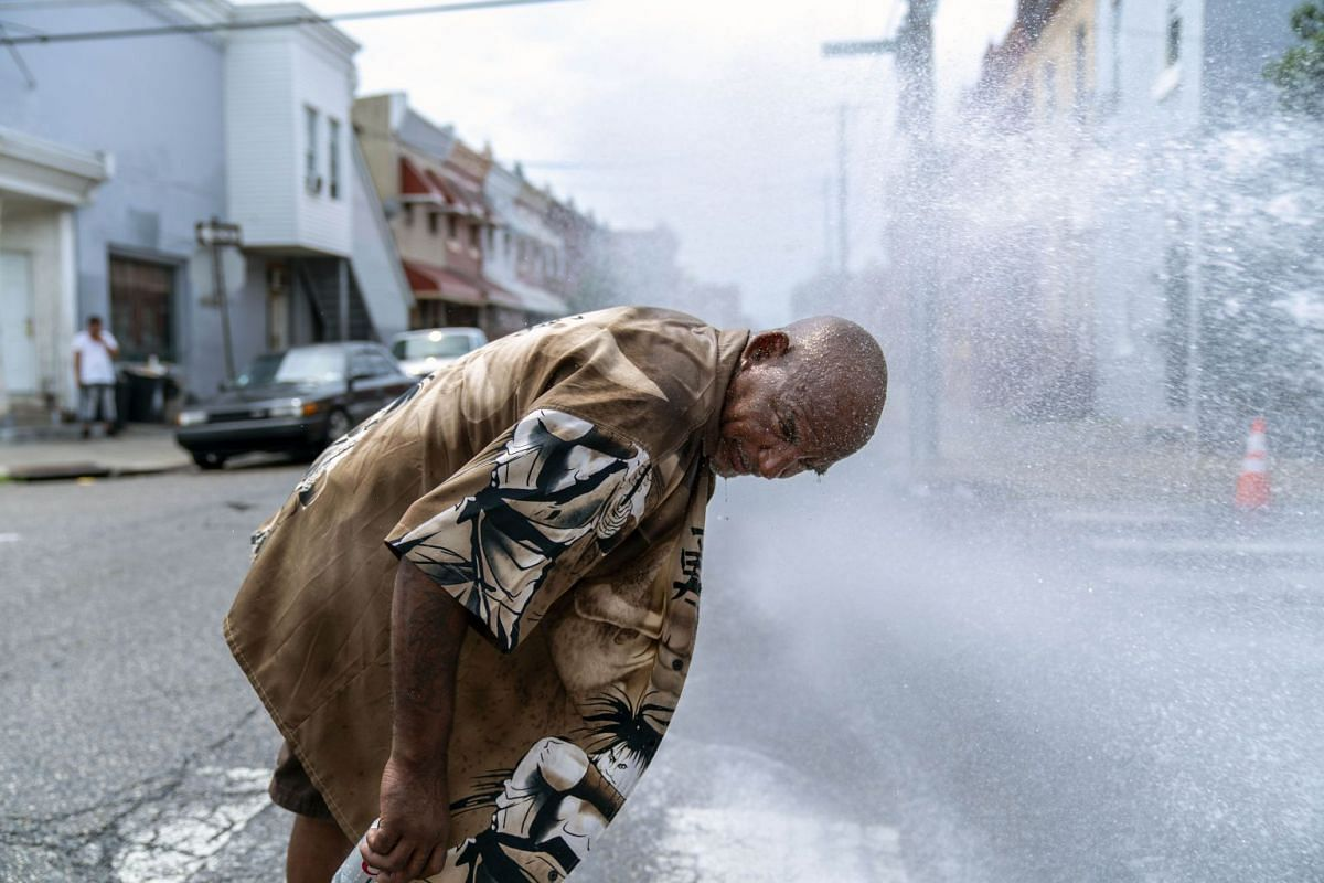 A man cools off in the spray of a fire hydrant during a heatwave on July 1, 2018, in Philadelphia, Pennsylvania.