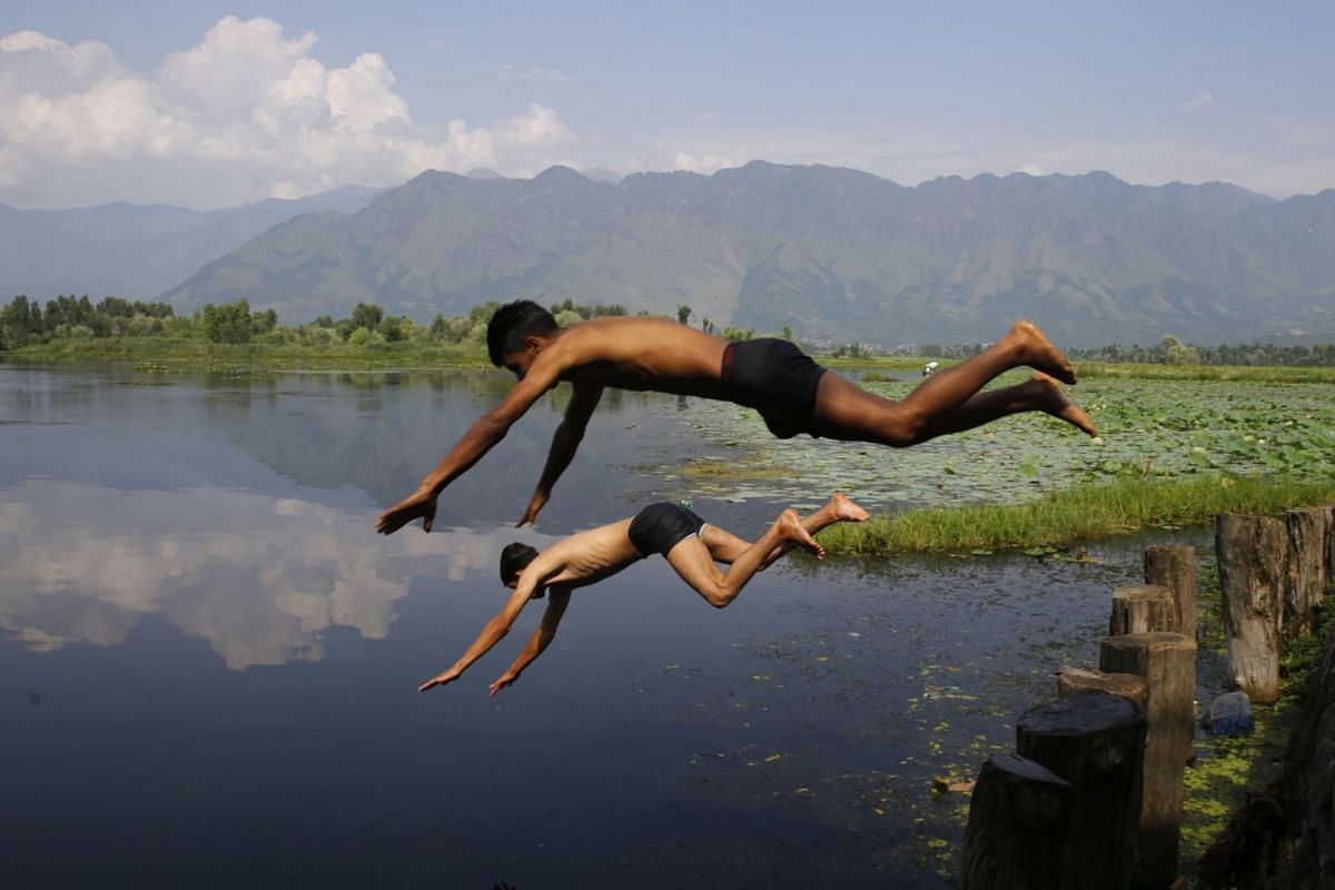 Kashmiri boys jump into the waters of Nigeen Lake to beat the heat in Srinagar, the summer capital of Indian Kashmir, on July 16, 2018.
