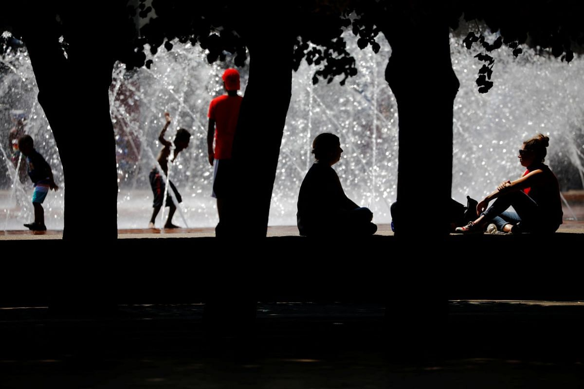 People sitting in the shade to cool off at a fountain during a summer heat wave in Boston, Massachusetts, on July 2, 2018.