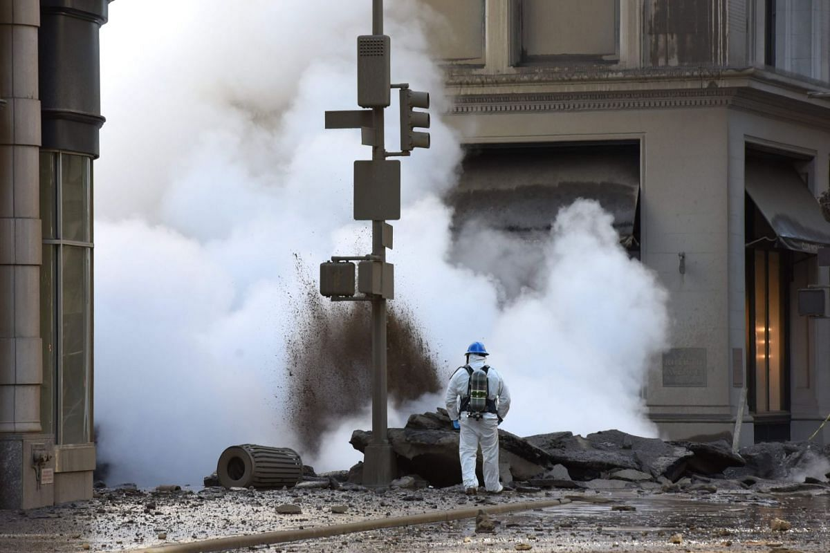 A worker looks at steam coming from 5th Avenue after a steam explosion tore apart the street in the Flatiron District of New York on July 19, 2018. PHOTO: AFP