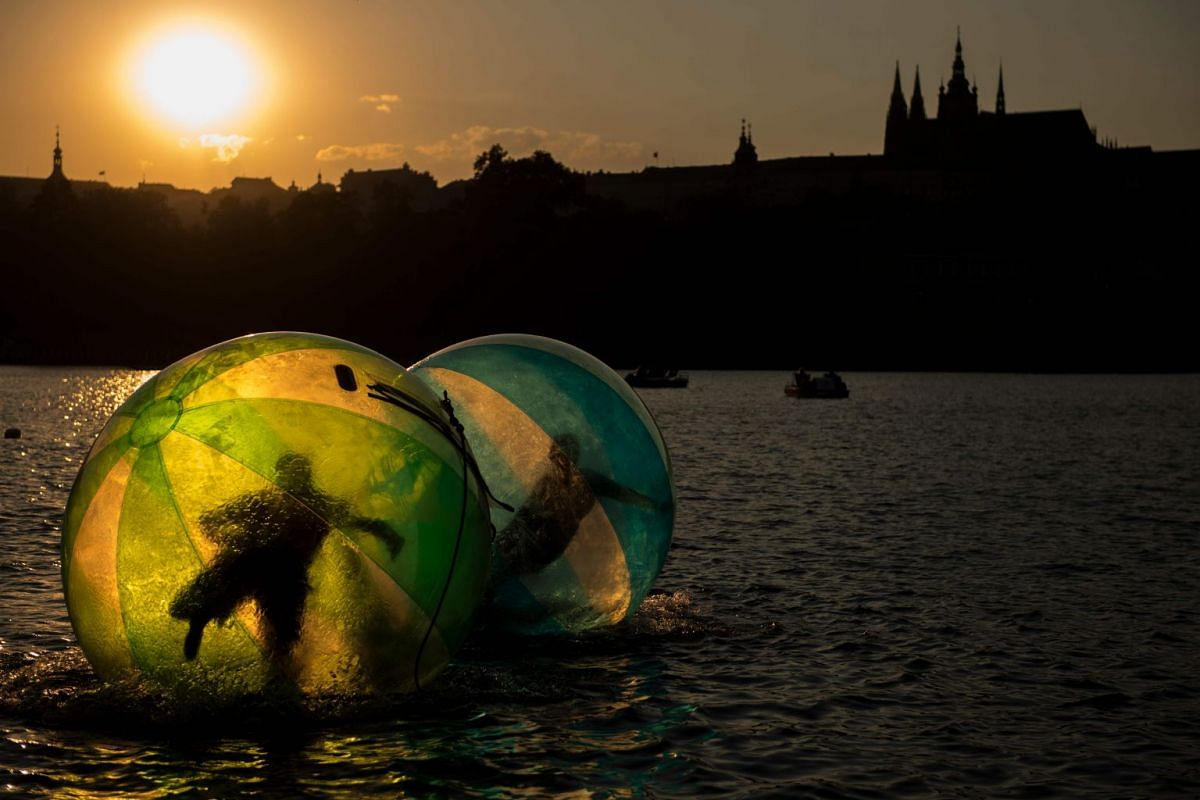 Tourists try out zorb balls on the Vltava river on July 19, 2018 in Prague. PHOTO: AFP