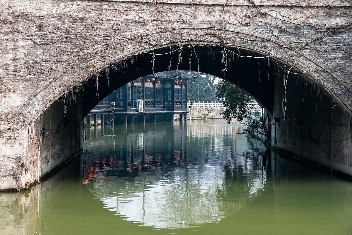 A man doing taiji in front of Changsheng Pavilion. Dongguan Street (above) dates back 1,200 years. Yechun Teahouse (left), seen through the arch of a bridge. A father and son enjoy the scene of the Heyuan in Yangzhou with its traditional style of arc