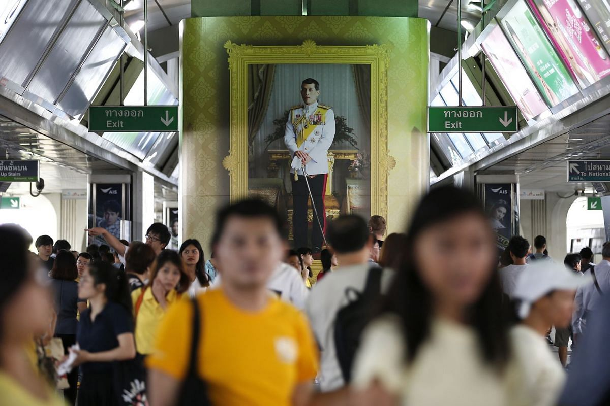 People walk past a large picture of Thai King Maha Vajiralongkorn Bodindradebayavarangkun displayed in recognition of King Maha Vajiralongkorn's birthday celebrations at a station in Bangkok, Thailand, 23 July 2018. Thais across the country will cele