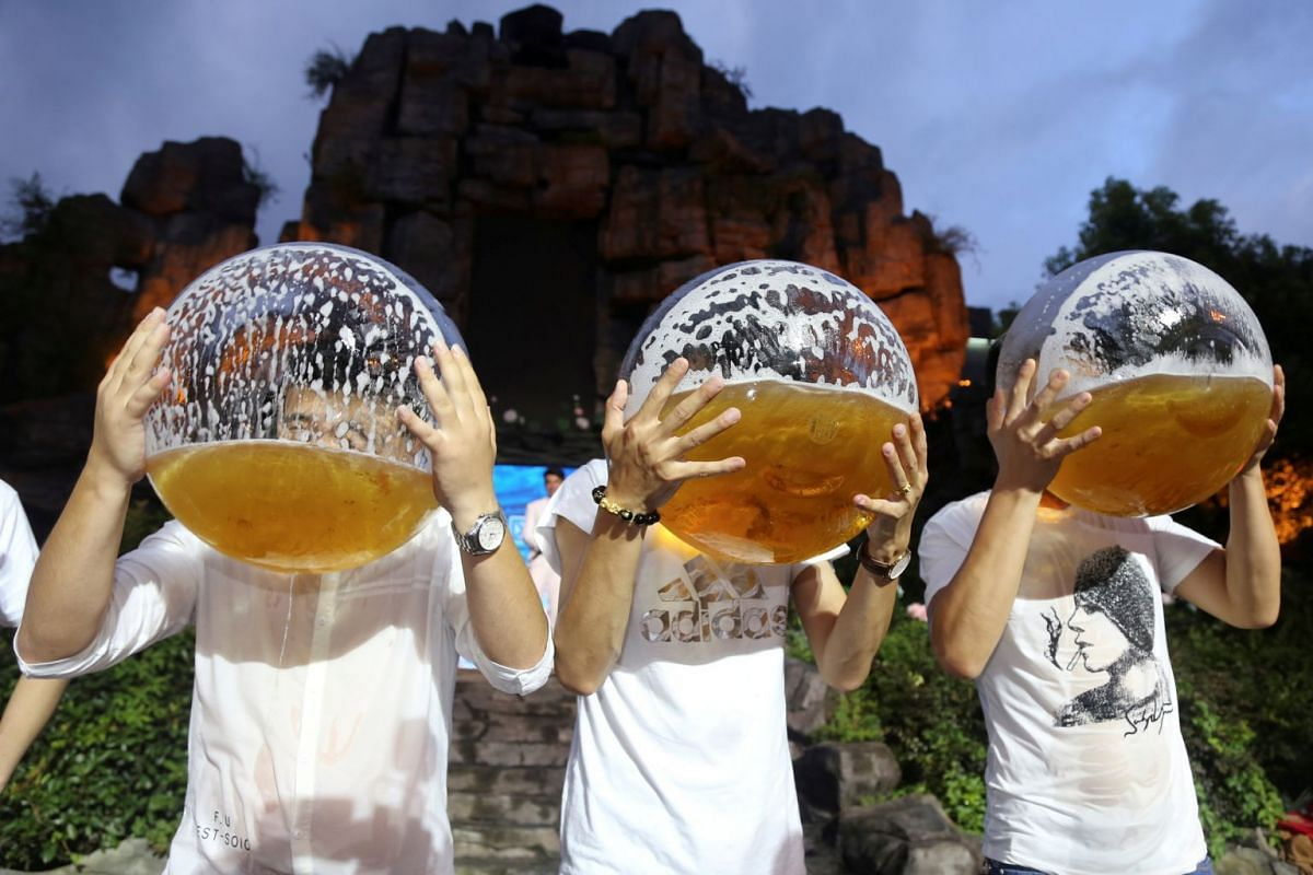 People drink beer from fish bowls at a beer drinking competition in Hangzhou, Zhejiang province, China July 21,2018.