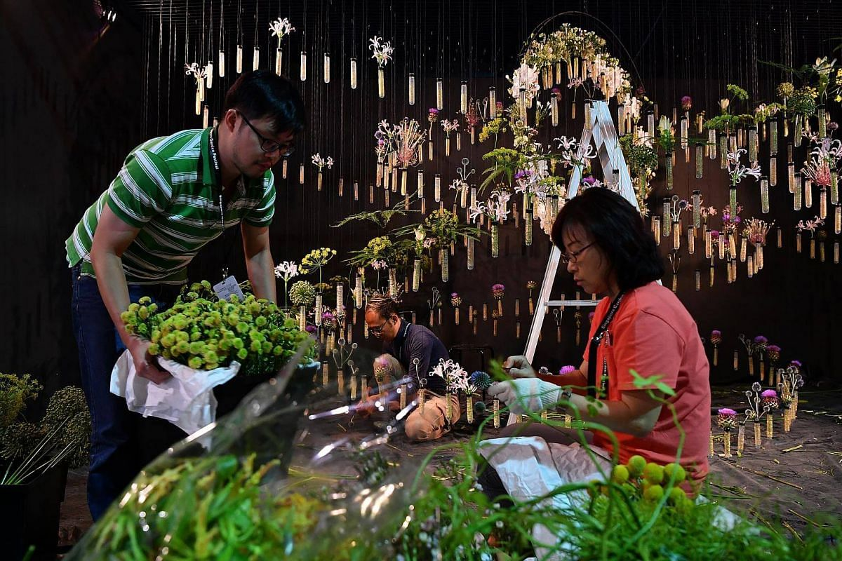 Mr Toh Hong Yuan, (left) preparing cut flowers with Ms Ivy Tay, (right) Freelance Florist, on the last day of setup for the floral window display at Gardens by the Bay, on July 19, 2018