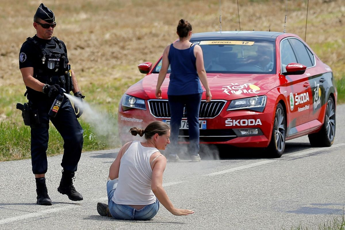 A police officer pepper sprays a protester as another protester stands in front of the race director's car on July 24, 2018 during the 218-km Stage 16 of Tour de France cycling race from Carcassonne to Bagneres-de-Luchon .
