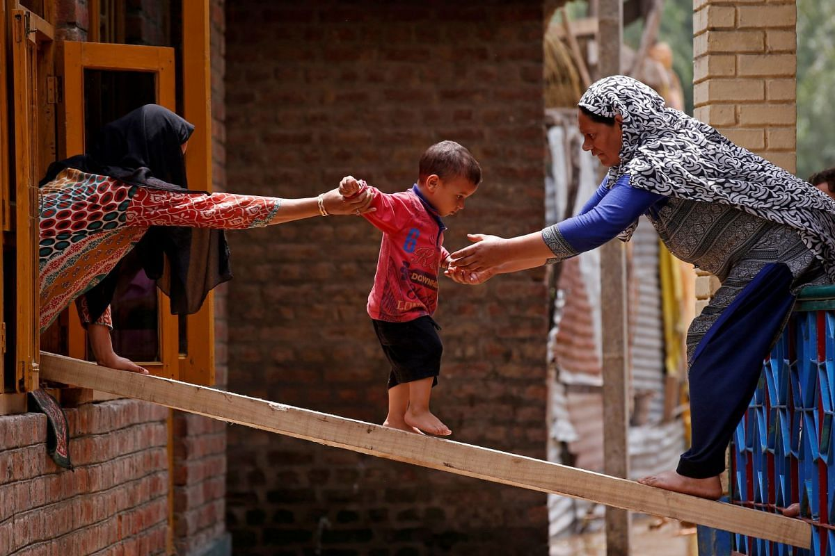 Women help a child to cross over to the other house on a wooden plank after flash floods in Tailbal, on the outskirts of Srinagar, India, July 24, 2018.