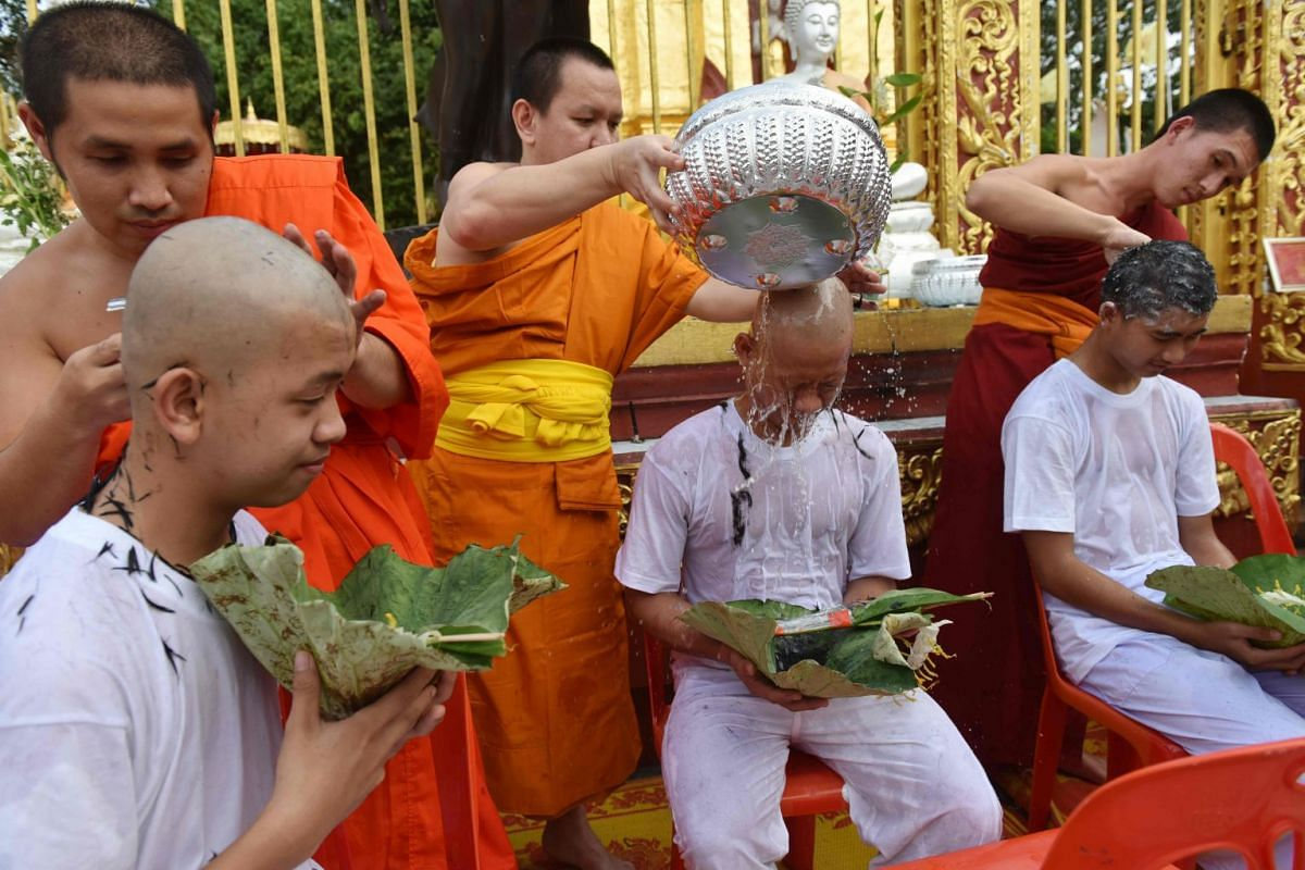 """Buddhist monks shave the hair of the rescued Thai boys and members of """"Wild Boars"""" football team together with their coach at the Phra That Doi Wao Buddhist temple in the Mae Sai district of Chiang Rai province during the religious ordination ceremon"""