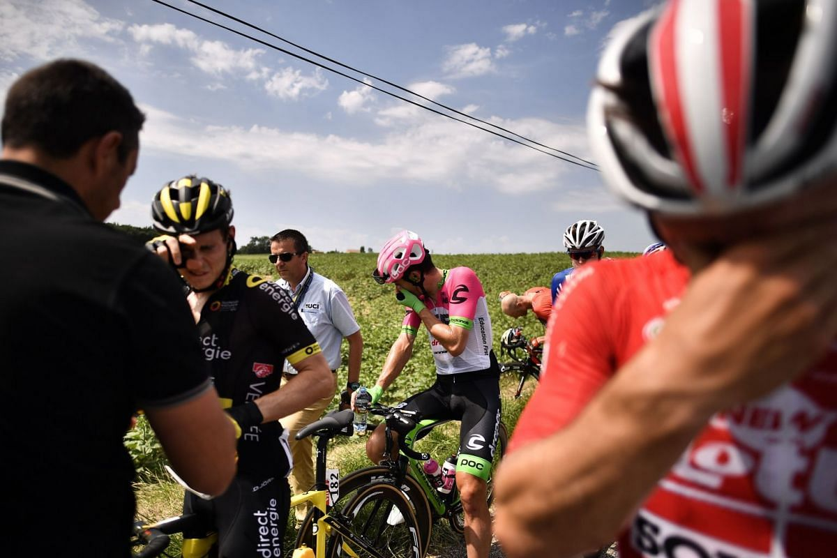 Riders clean their eyes after tear gas was used during a farmers' protest who attempted to block the stage's route, during the 16th stage of the 105th edition of the Tour de France cycling race, between Carcassonne and Bagneres-de-Luchon, southwester