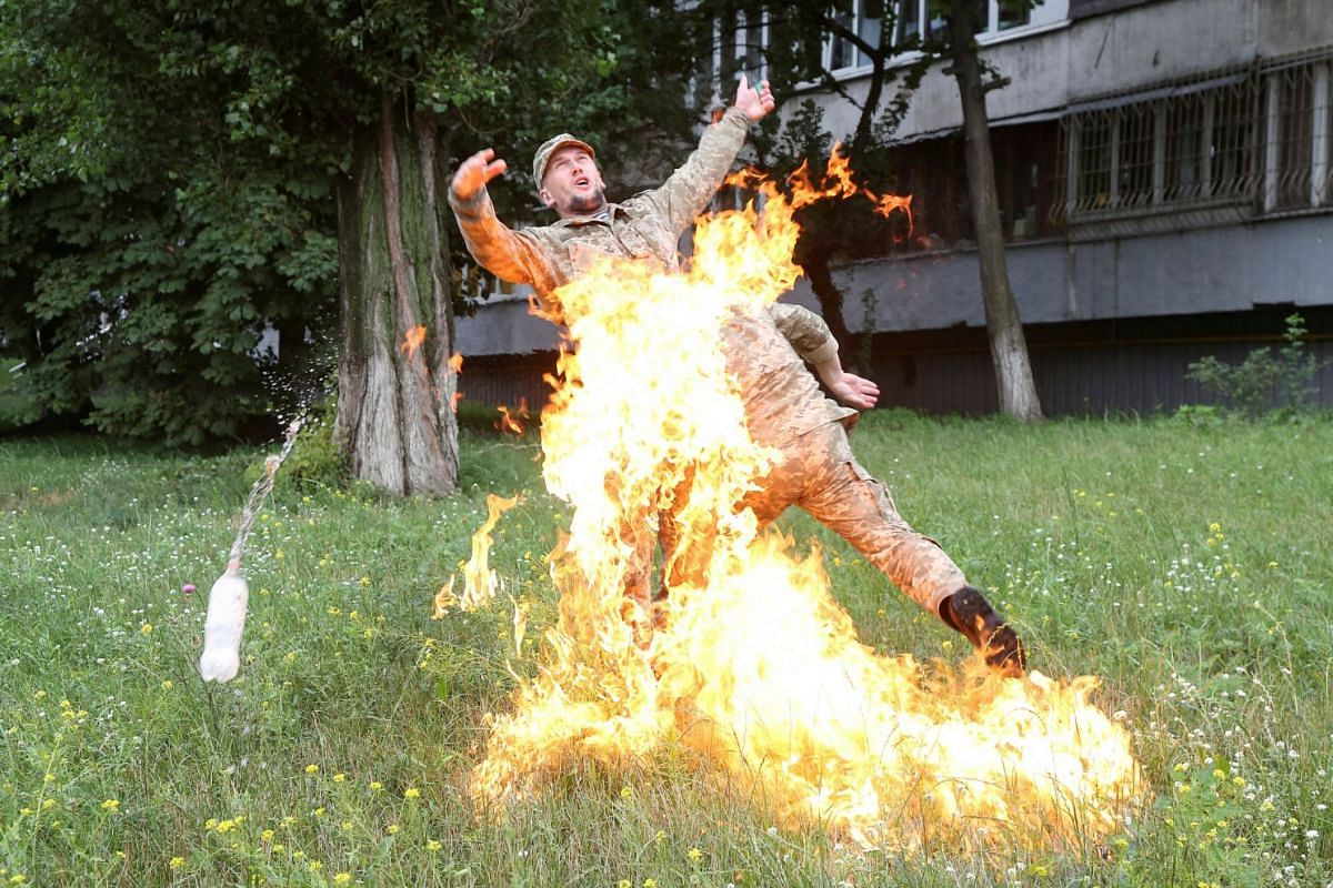 An officer on duty (right) attempts to knock down the flame as Ukrainian former serviceman Serhii Ulianov sets himself on fire while protesting against his dismissal from the Armed Forces in front of the Ukrainian Defence Ministry headquarters in Kie