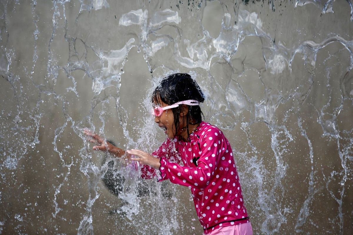A girl plays in a fountain to cool down at a park during a hot summer day in Tokyo, Japan, July 26, 2018.