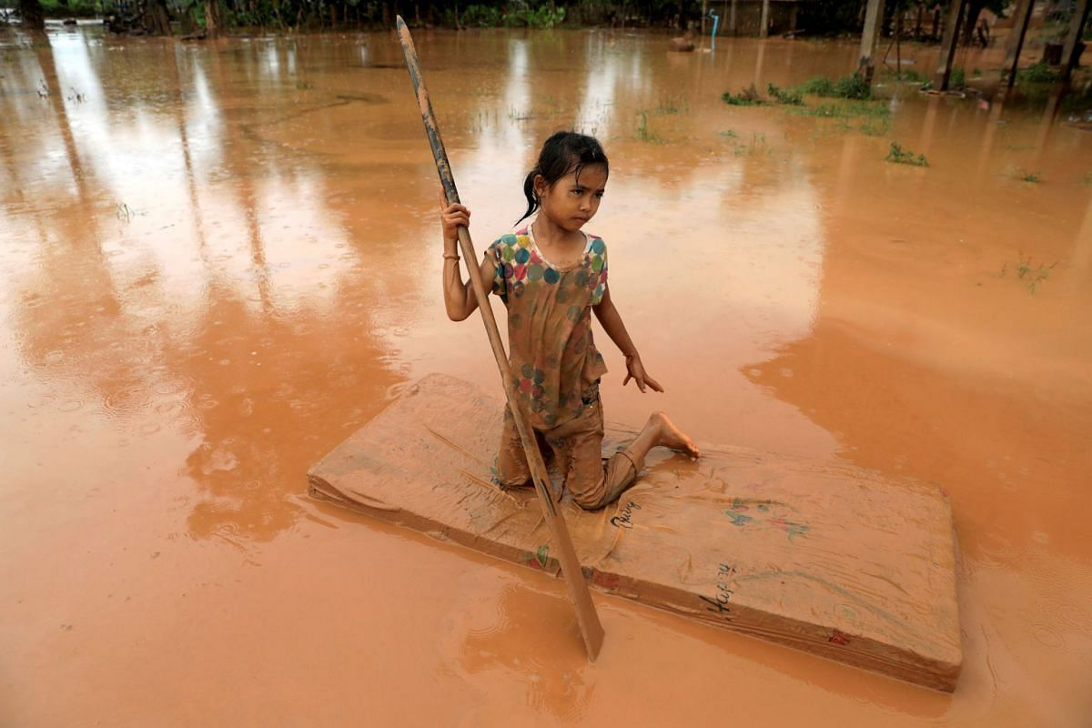 A girl uses a mattress as a raft during the flood after the Xepian-Xe Nam Noy hydropower dam collapsed in Attapeu province, Laos July 26, 2018.