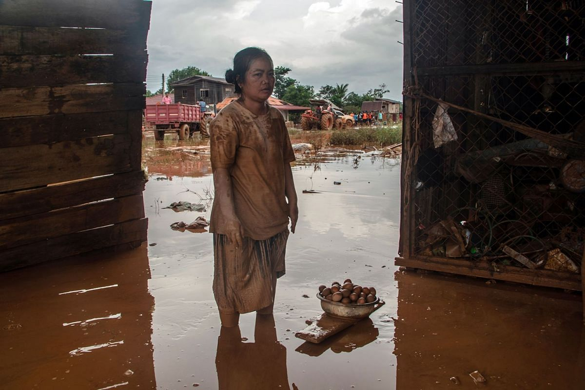 A woman surveys the damage to her home upon her return to the flooded town of Khom Kong, Laos, on Thursday, July 26, 2018. The United Nations has said that eight villages were affected by the flooding after an auxiliary dam, part of a billion-dollar