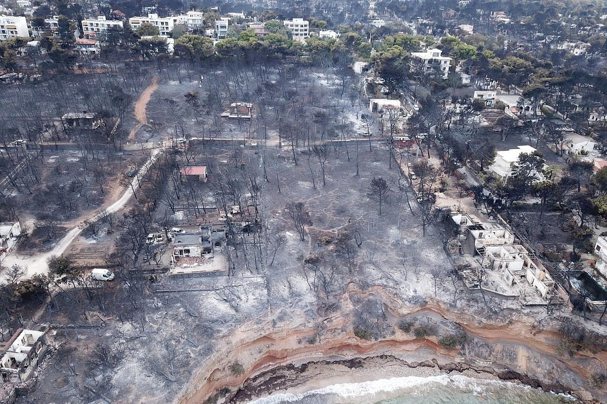 A house yesterday caught in the fast-moving fire in northern California that has destroyed dozens of homes. An aerial view of Mati in Greece after a devastating wildfire earlier this week.