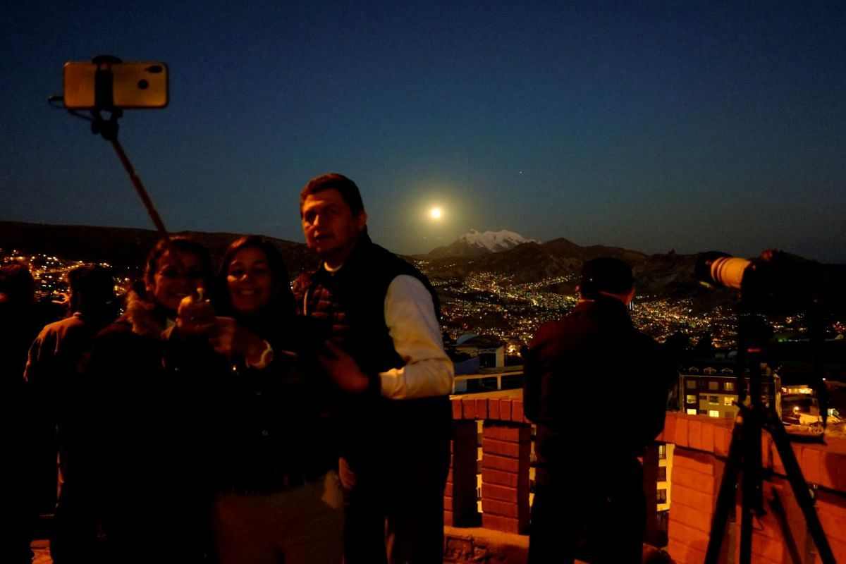 People taking a selfie with the moon during a full lunar eclipse in La Paz, Bolivia, on July 27, 2018.