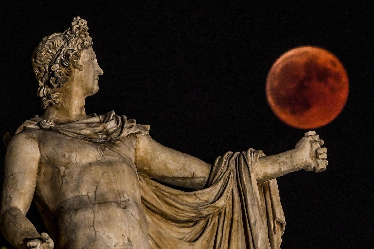 The 'blood moon' eclipse is seen beside a statue of the ancient Greek god Apollo in central Athens, on July 27, 2018.