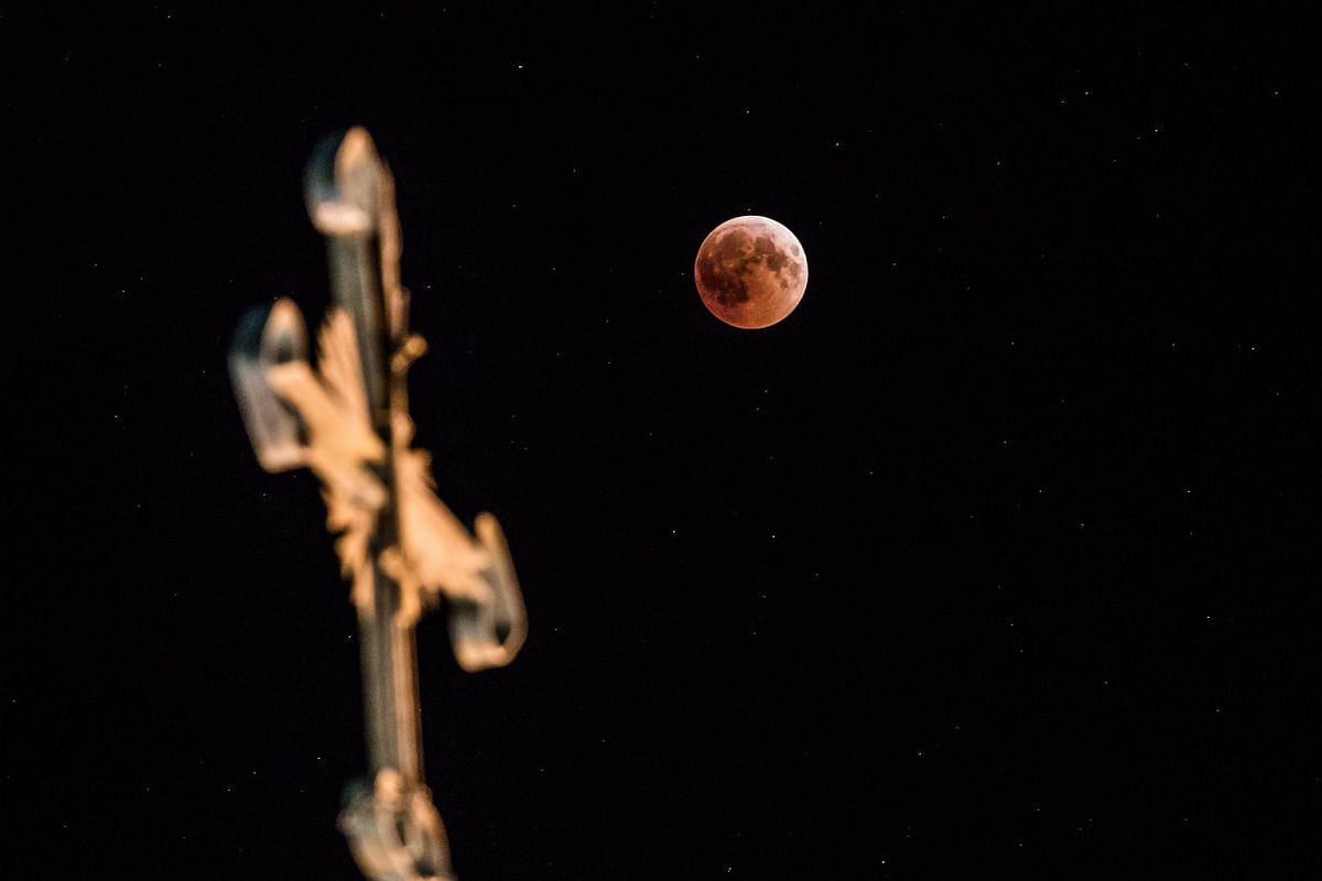 The 'blood moon' eclipse is seen beside the cross of the Mor Mikhail Church in Mardin, on July 27, 2018.