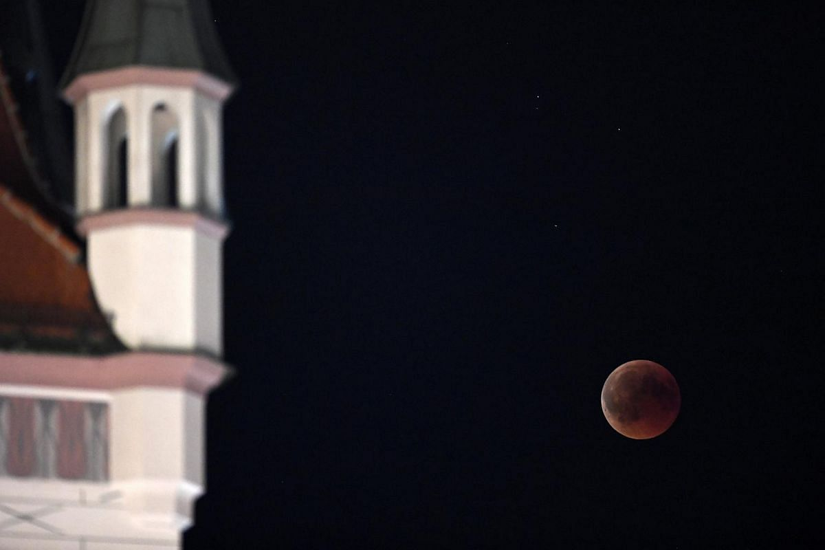 A 'blood moon' is seen during a full lunar eclipse next to the old city hall in Munich, Germany, on July 27, 2018.