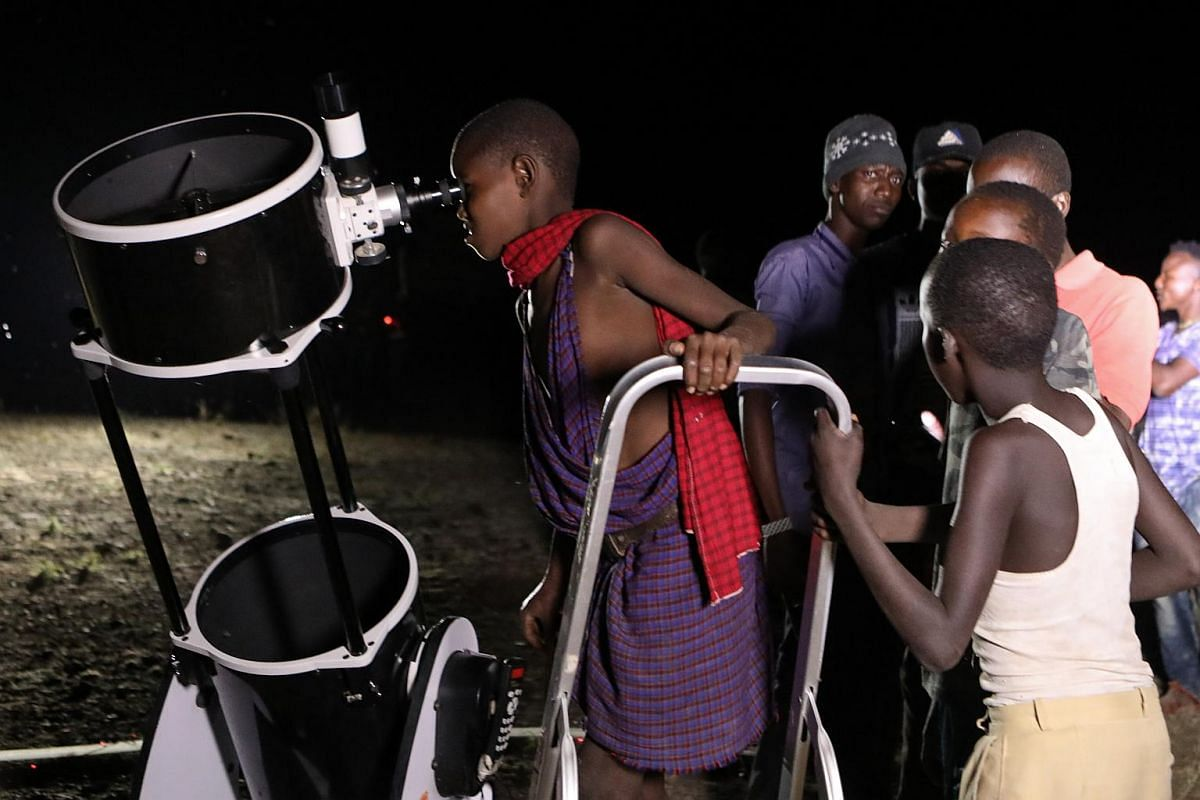 A Kenyan young boy (centre) looks through a telescope as the moon turns red in Oloika town, Magadi, on July 27, 2018.