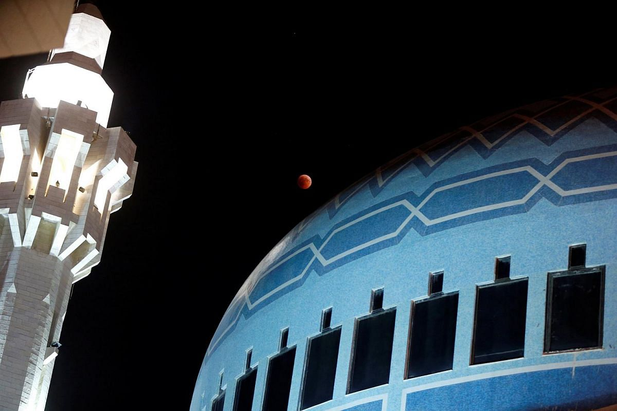 The moon is seen during a lunar eclipse over King Abdullah Mosque in Amman, Jordan, on July 27, 2018.